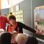 Schulbiene zeigt Schüler auf Plakat den Bestäubungsvorgang