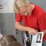 Schulimker Reinhold zeigt in einem Buch eine Blume, die von einer Biene besucht wird.