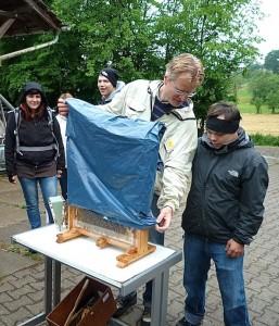 Imker Reinhold und Michael, ein Jungendlicher, enthüllen des Bienenschaufenster