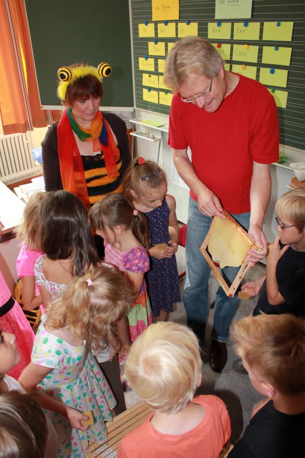 Schulimker Reinhold zeigt den Schülern ein Naturwabenbau-Rähmchen