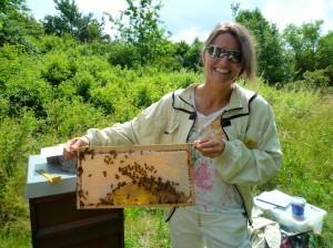 Bienenpatin Felicitas Sauer hält ein Honigrähmchen mit Bienen hoch