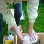 Reinhold füllt Zuckerwasser in einen Tetrapack im Bienenstock auf