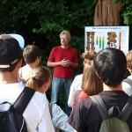 Schulimker Reinhold Burger vor Lehrtafel mit stehenden Schülern