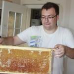 Philipp hält eine Honigwabe in die Höhe