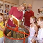 Reinhold zeigt eine Honigwabe, Gäste stehen um Honigschleuder