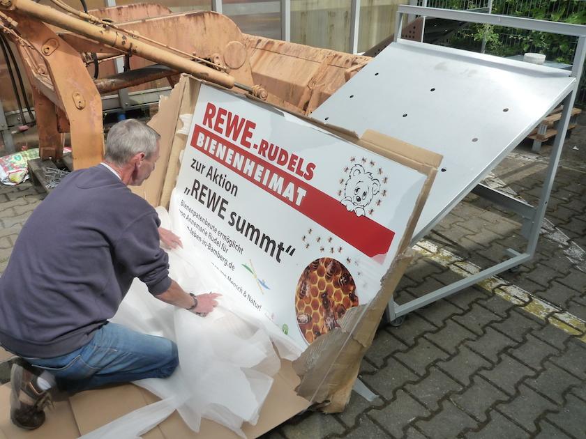 """Montage des REWE-Schildes """"Bienenheimat"""""""