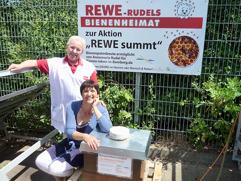 Bienenpatin Annemarie Rudel und Ilona Munique stehen vor neuer Bienenheimat im REWE-Markt