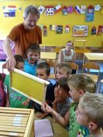 Reinhold zeigt Kindern eine Mittelwandwabe aus der Lehrbienenbeute