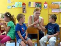 Kinder und Erzieherin kosten Honig
