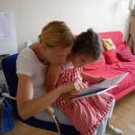 Lola betrachtet, auf Katharinas Schoß sitzend, ein Insektenbilderbuch