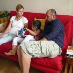 Lola zwischen Katharina und Papa, ein Bienenbilderbuch betrachtend