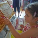 Lola hält ihr Löffelchen bereit, um aus der Honigwabe zu naschen