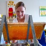 Katharina entdeckelt eine Honigwabe