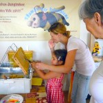 Katharina hilft Lola beim Entdeckeln der Honigwabe