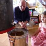 Papa und Lola sehen zu, wie der Honig aus der Schleuder in den Topf fließt