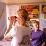 Katharina misst den Wassergehalt des Honigs mit einem Refrakometer