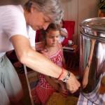 Oma Gabi hilft Lola beim Abzapfen des Honigs