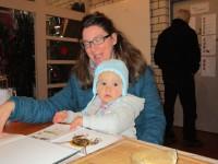 Mutter mit Kleinkind sieht Bilderbuch an