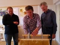 Erik Hanen beim Honigentdeckeln, flankiert von Mario und Reinhold