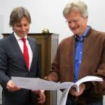 Matthias Polz und Reinhold Burger betrachten Bauplan Bienen-InfoWabe