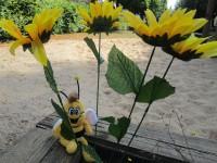 Plüschbiene Willi im Sandkasten an der Weide mit Sonnenblumen