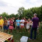 Studentengruppe wird von Reinhold Burger ins Honigernten eingewiesen