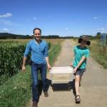 Heiko und Wenzel tragen die Honigernte zum Auto