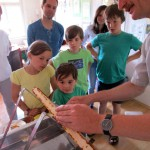Reinhold Burger demonstriert das Entdeckeln einer Honigwabe