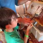 Jakob entdeckelt eine Honigwabe