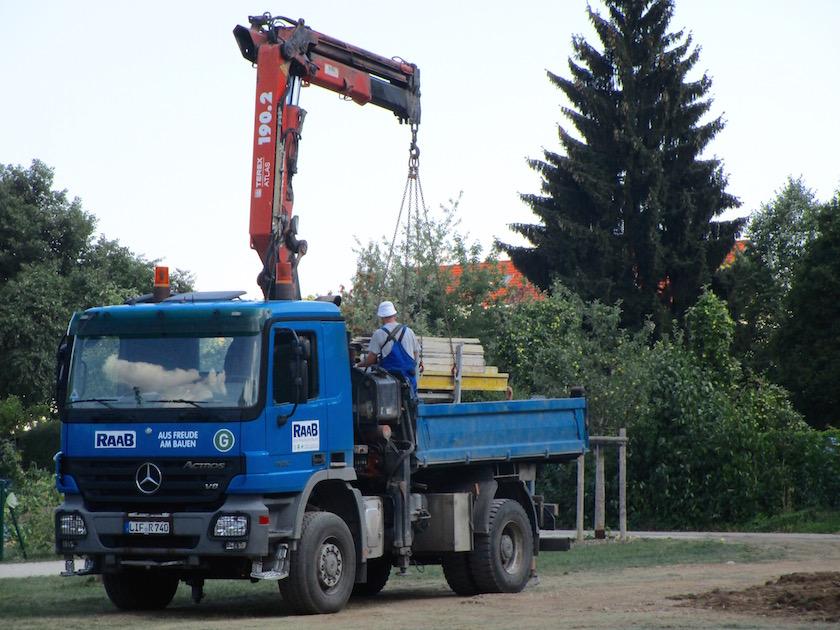 Kran hebt Baustellenmaterial auf Lader