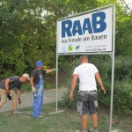 Baustellenschild von Raab-Bau wird aufgestellt