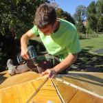 Jonathan zieht letzte Schrauben auf dem Dach der Bienen-InfoWabe an
