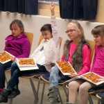 Schüler betrachten ein Bienensachbuch