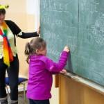 Grundschülerin zeichnet ein Hexagon an die Tafel