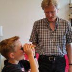 Kind misst den Wassergehalt des Honigs mit einem Refraktometer