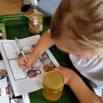Kind beschriftet das Honigglas-Etikett