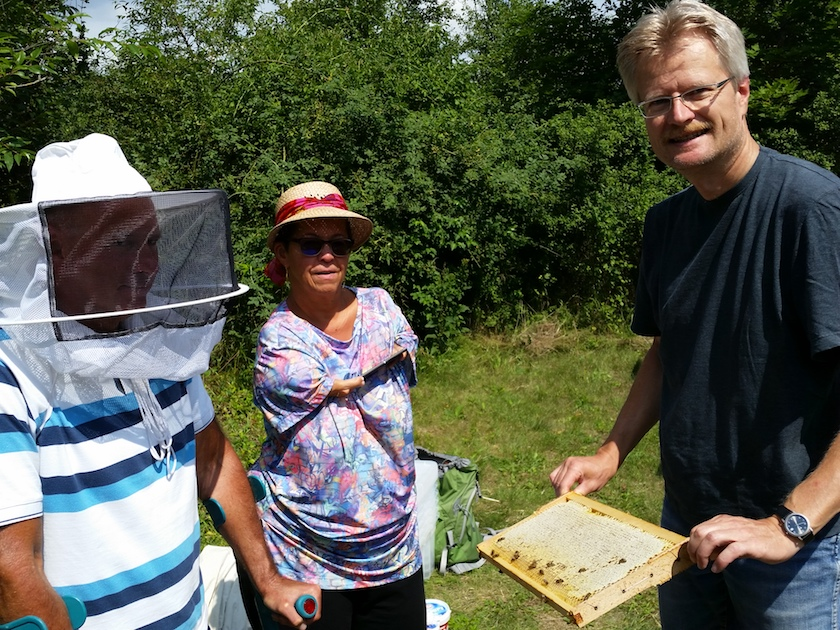 Reinhold zeigt den Bienenpaten Anne und Hans Zirkel eine Honigwabe