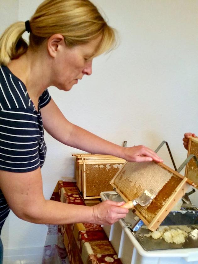 Rita entdeckelt eine Honigwabe