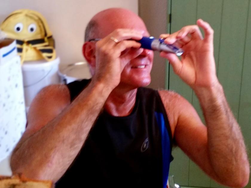 Hans misst den Wassergehalt des Honigs mit einem Refraktometer