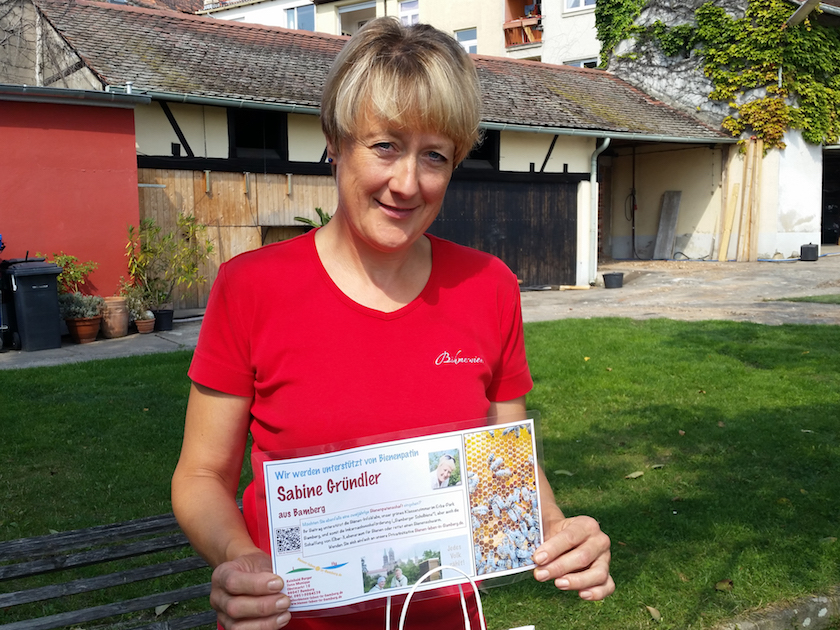Sabine Gründler mit Bienenpatenschild