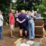 Gruppe schaut in die offene Bienenbeute