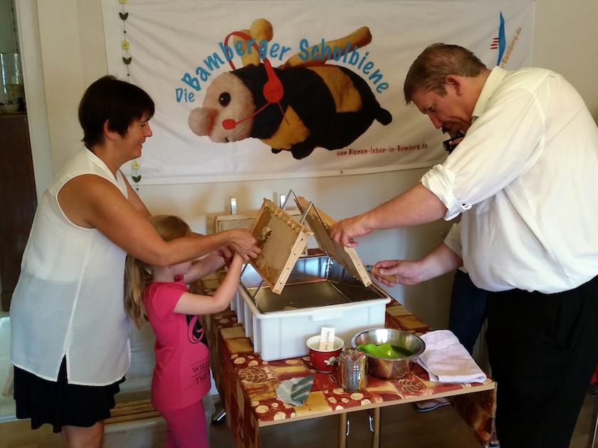 Ilona Munique hilft dem Töchterlein von Andreas Schwarz beim Entdeckeln der Honigwabe.