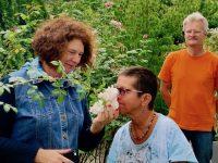 Anne riecht an Rosenblüte