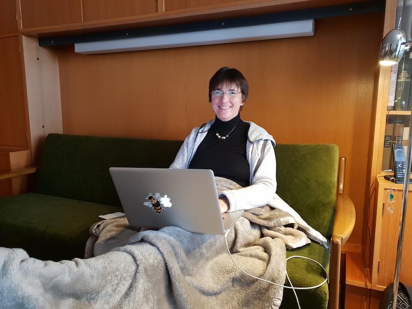 Ilona beim Arbeiten, mit Kuscheldecke
