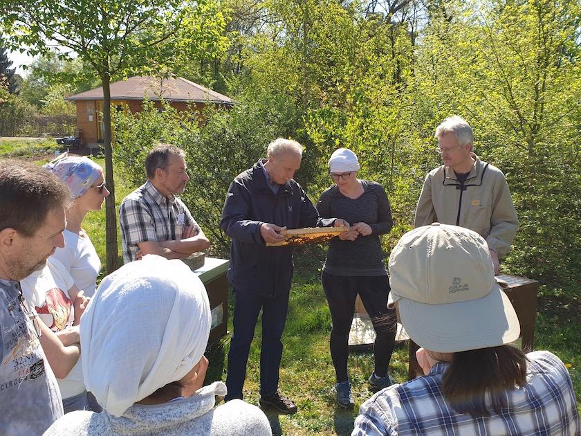 Teilnehmer am Imkerkurs mit Wabe